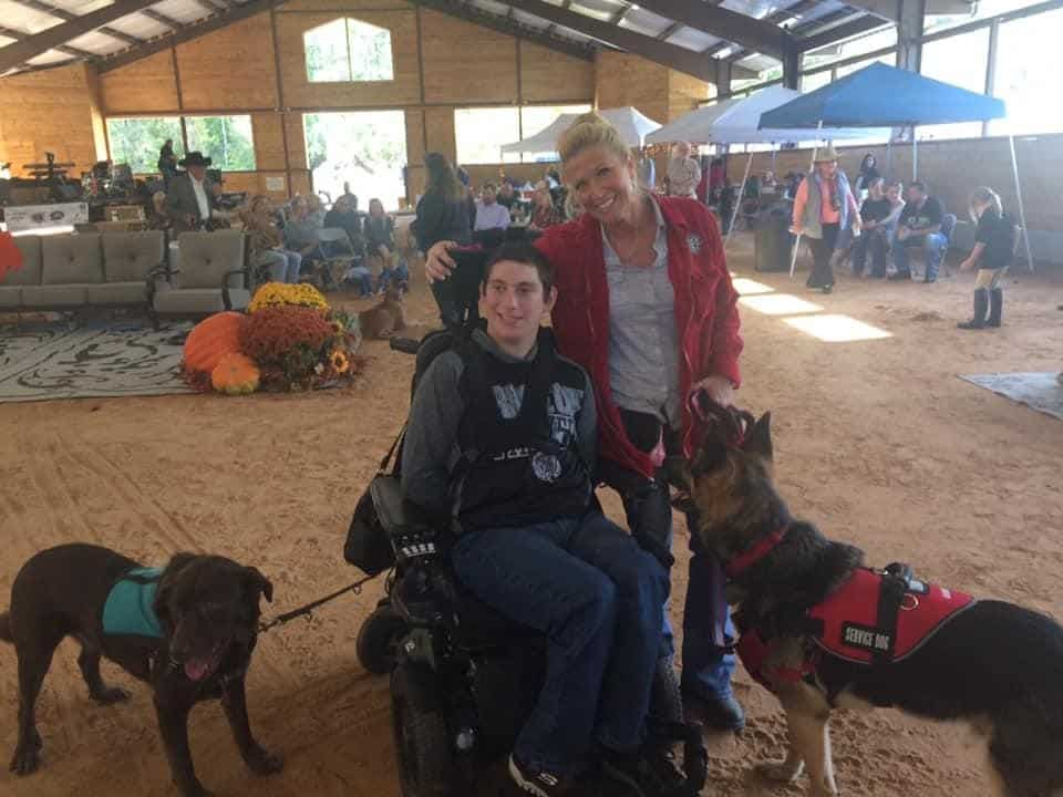 Tracy with TJ and service dogs at a fundraiser